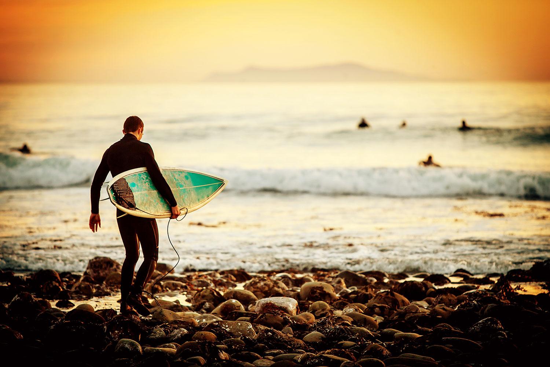 Surfer walking over rocks at sunset