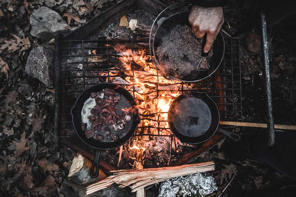 Cooking outdoors over campfire