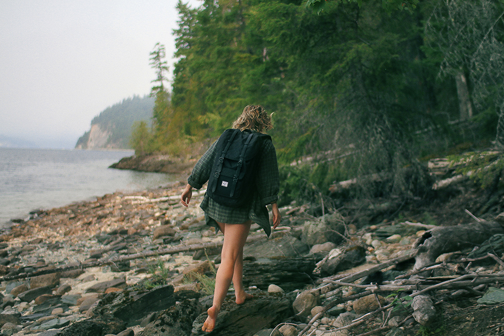 Woman exploring a lakeside with no shoes on